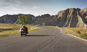 Motorcycle riding down the road with a tree and beautiful buttes in the background