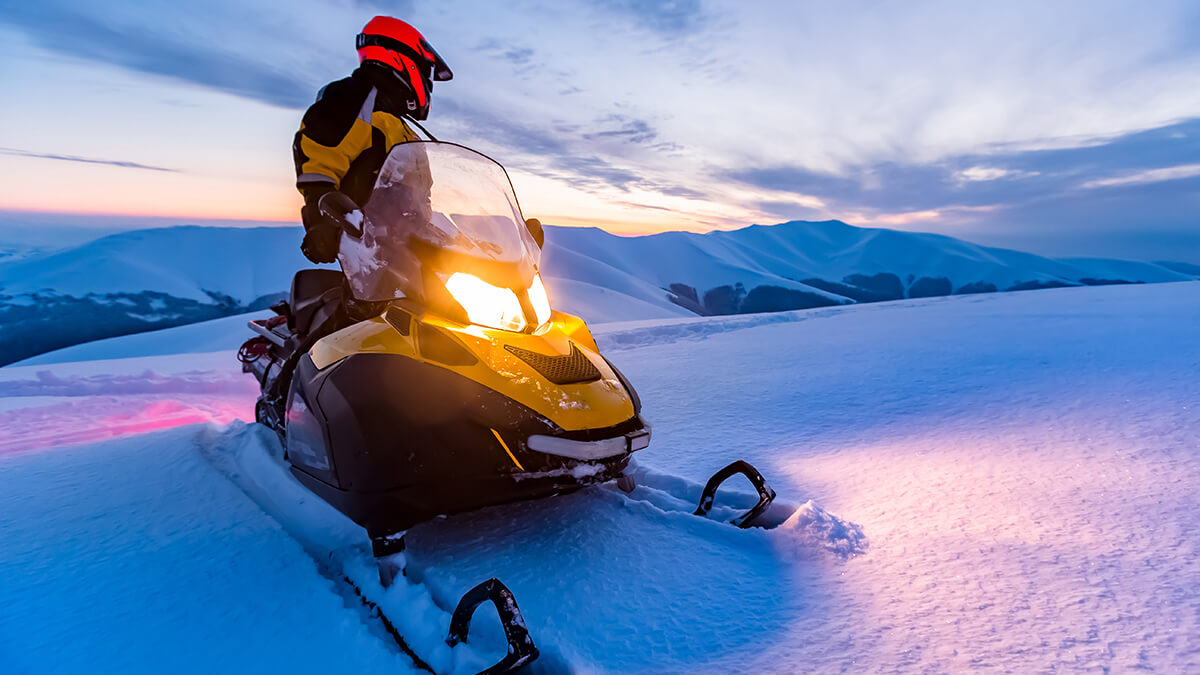 A group of snowmobilers riding through snow