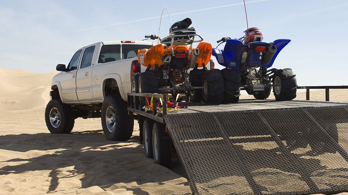 Two ATVs loaded on a trailer attached to a large white pickup truck parked amoung sand dunes.