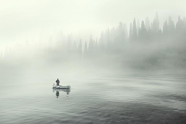 A fisherman in a canoe fishing in the frigid morning