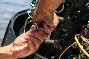 A close-up of hands adjusting something on a boat engine