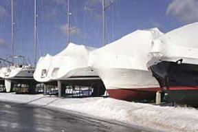 A row of boats covered with winterizing plastic