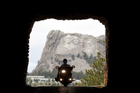 Motorcycle riding through tunnel with Mount Rushmore in the background
