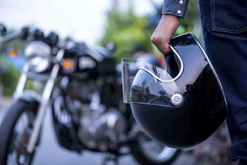 A biker approaching a motorcycle with helmet in hand