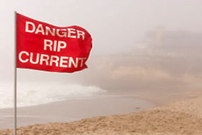 A warning flag on beach to alert swimmers of rip currents