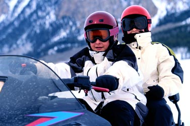 A close-up of two snowmobilers riding in tandem