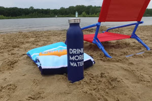 A water bottle near a towel and beach chair on the beach