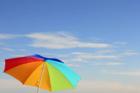 A beach umbrella with blue skies behind it